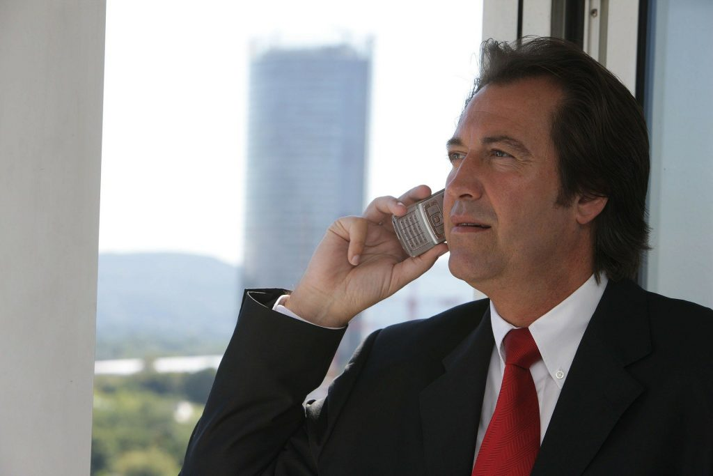 Businessman standing at the window and talking on the phone