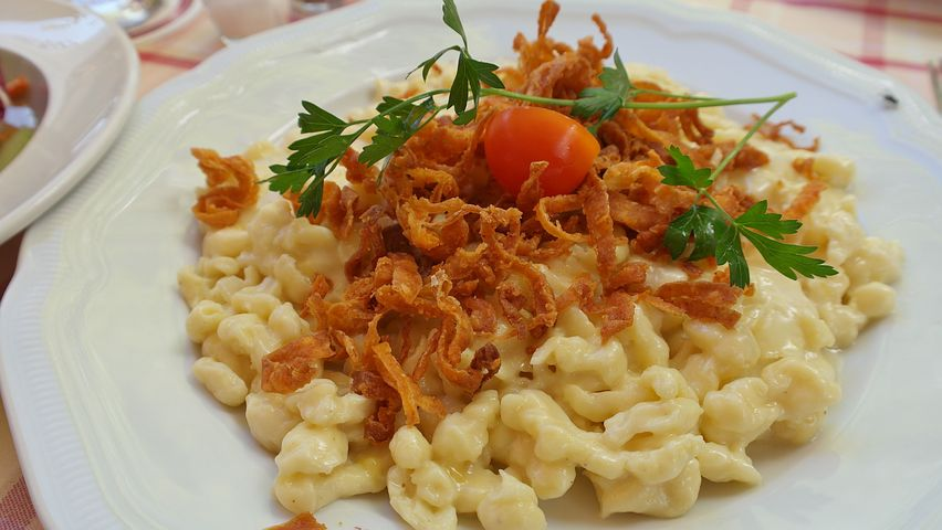 A classic German meal of spätzle a creamy pasta topped with fried onions, and a garnish consisting of parsley and a cherry tomato