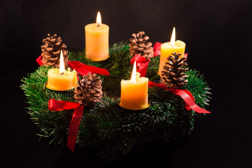 A pine wreath with candles glowing in the dark.