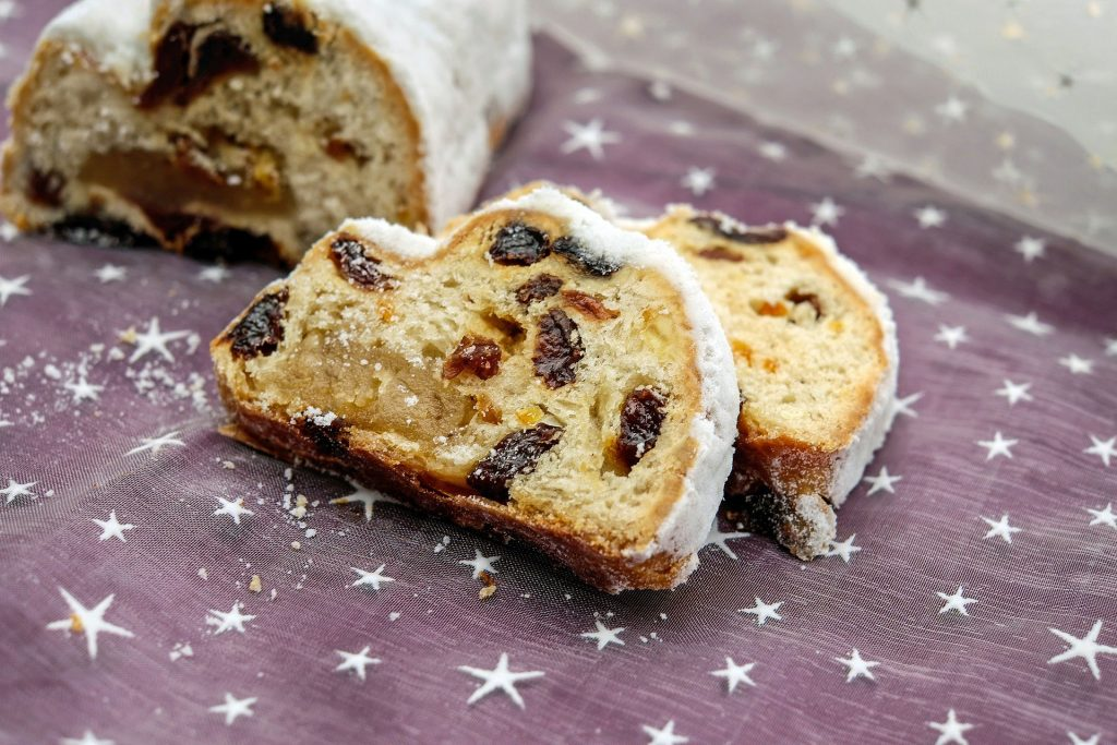 A loaf of traditional German Christmas cake filled with raisins with two slices cut off.