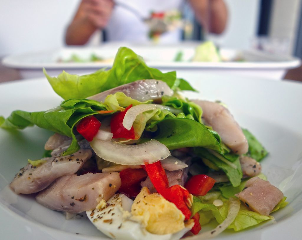 A classic German salad with greens, fish, onions, and hard boiled eggs.