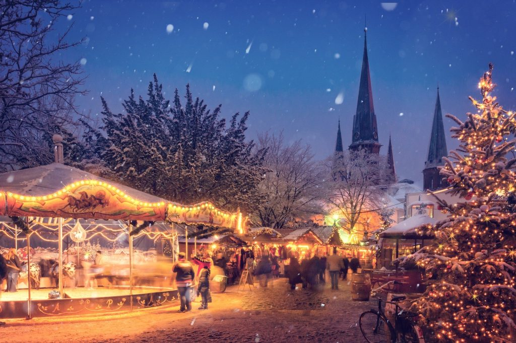 A traditional German Christmas market scene under a starry sky. There is a Christmas tree in the foreground and a church behind the market.