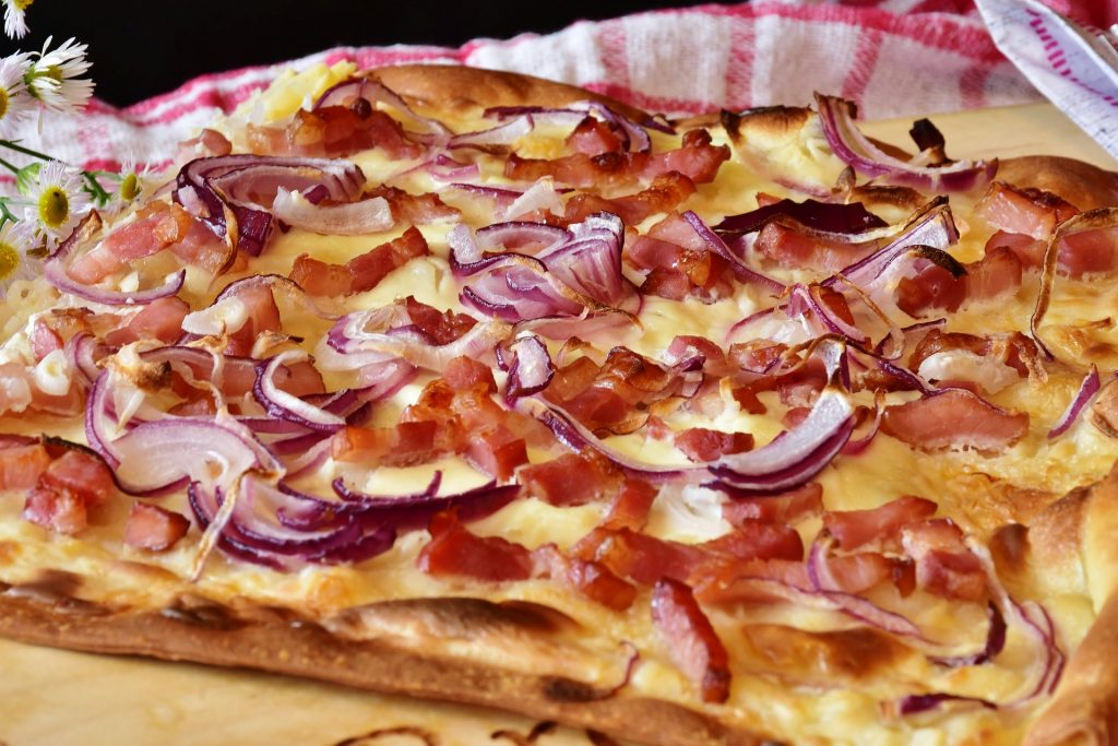 A savory tart topped with red onions and bacon.